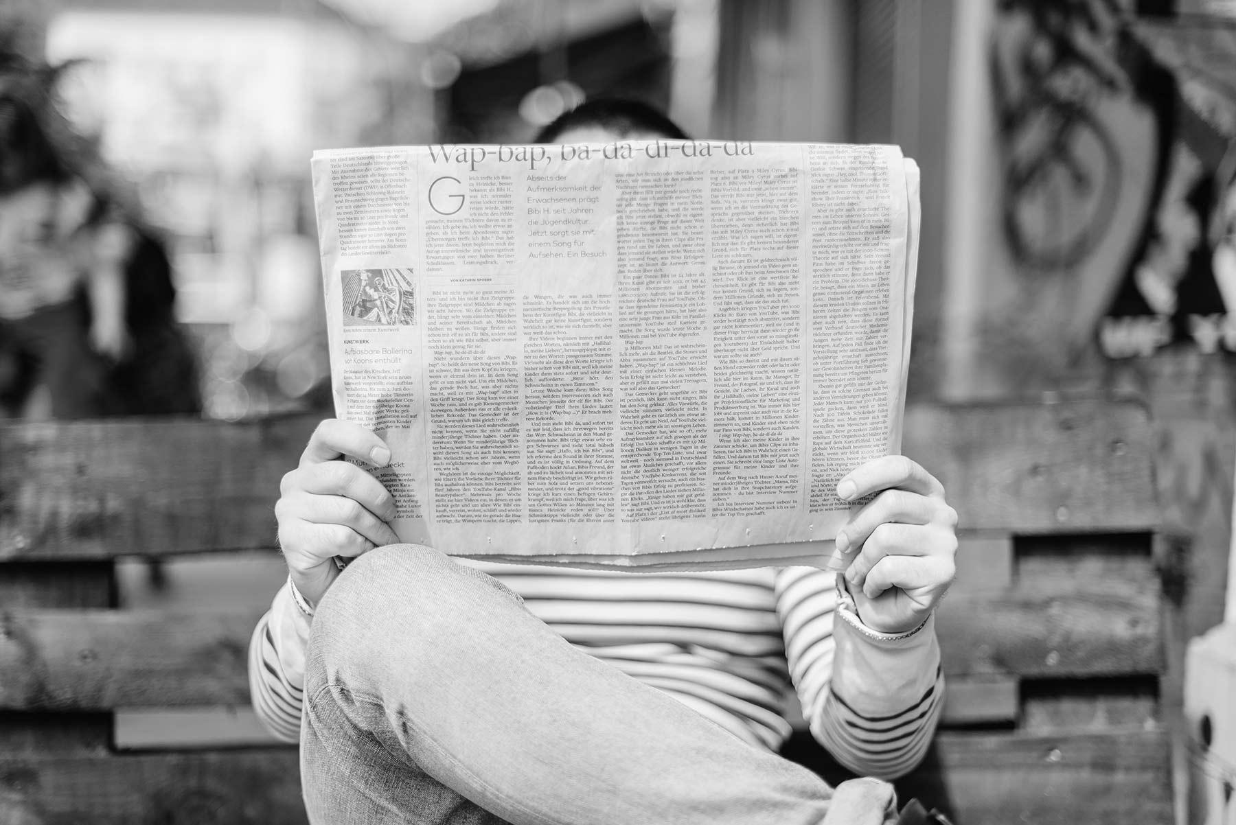 iemand leest de krant op de bank